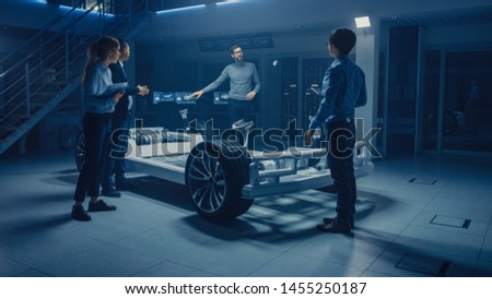Automobile Engineers Working on Electric Car Platform Chassis, Using Tablet Computers with CAD Software for 3D Concept. In Automotive Innovation Facility Vehicle Frame with Wheels, Engine and Battery #1455250187