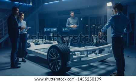 Automobile Engineers Designing Electric Car Platform Chassis Prototype, Using Tablet Computers with CAD Software for 3D Concept. In Automotive Innovation Facility Vehicle Frame with Wheels, Engine #1455250199