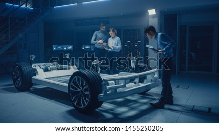 Diverse Automobile Engineers Talking while Working on Electric Car Platform Chassis Prototype. In Automotive Innovation Facility Concept Vehicle Frame Includes Tires, Suspension, Engine and Battery #1455250205
