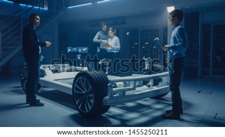Automobile Design Engineers Working on Electric Car Platform Chassis Prototype, Using CAD Software for 3D Concept. In Automotive Innovation Facility Vehicle Frame with Tires, Suspension, Engine #1455250211