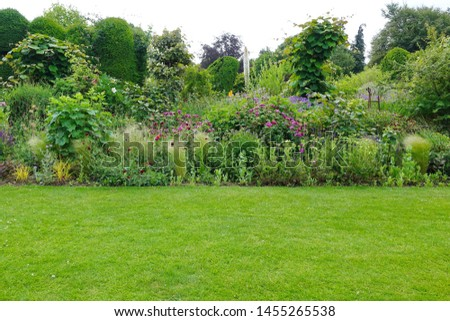 Scenic View of a Beautiful English Style Landscape Garden with a Green Mowed Lawn and Colourful Flower Bed #1455265538