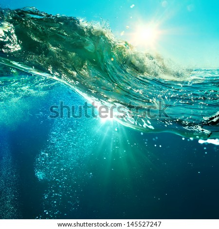 rough colored ocean wave breaking down at sunset time
