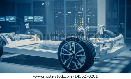 Automobile Engineers Discussing and Designing Electric Car Chassis Platform, Using Tablet Computers with 3D CAD Software. In Automotive Innovation Facility Vehicle Frame with Wheels Engine and Battery #1455278201