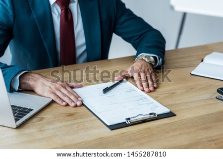 cropped view of recruiter sitting near laptop and clipboard on wooden table  #1455287810
