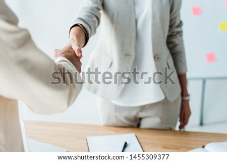 cropped view of recruiter and employee shaking hands while standing  in office  #1455309377