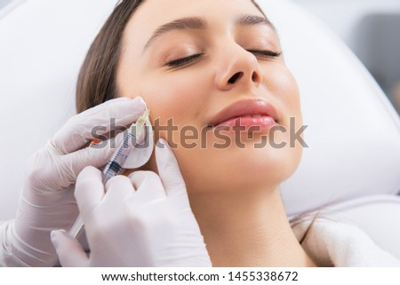 Anti-aging face treatment. Close up portrait of young smiling pretty woman having botox rejuvenation procedure of cheek zone by specialist #1455338672