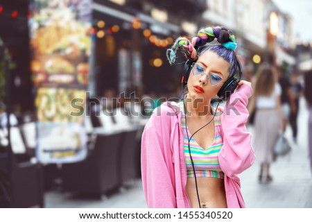 Cool funky young woman with trendy eyeglasses listening music on headphones outdoor - hipster girl with sunglasses and piercings enjoy music vibes – street fashion look with girl teen with crazy hair #1455340520