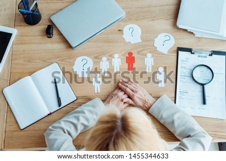 top view of woman with clenched hands near paper shapes and blank notebook on table  #1455344633