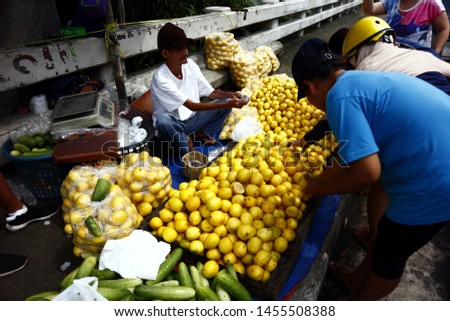 ANTIPOLO CITY, PHILIPPINES – JULY 17, 2019: A street vendor sells fresh and ripe lemon at a sidewalk along a highway. #1455508388