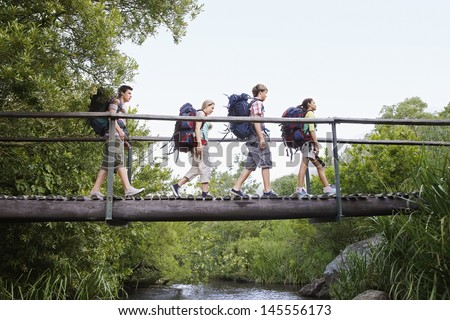Teenage boys and girls with backpacks walking on bridge in forest #145556173