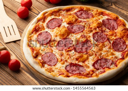 Delicious hot homemade Pepperoni pizza on the wooden table. Pepperoni Pizza - Fresh homemade pizza with pepperoni, cheese and tomato sauce on rustic black stone background with copy space. #1455564563