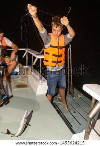 Phuket, Thailand - January 2018: Night barracuda big game fishing near Phuket island. Happy fisherman with caught fish. Sport fishing on local thai boat with lucky and happy people on vacation. #1455624215