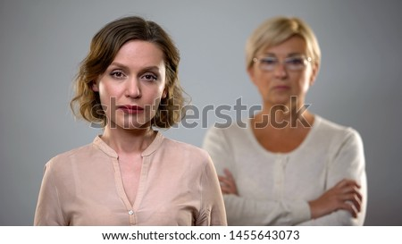 Sad young woman looking in camera, strict senior mother standing behind, problem #1455643073