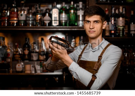 Attractive male bartender holding in hands a steel shaker on the bar counter in the dark blurred background #1455685739