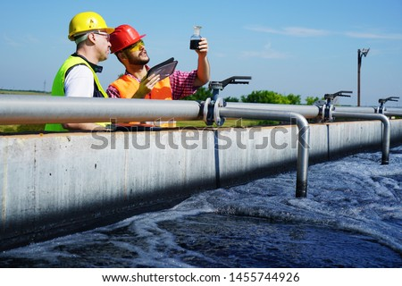 Engineers controlling a quality of water ,aerated activated sludge tank at a waste water treatment plant         Royalty-Free Stock Photo #1455744926