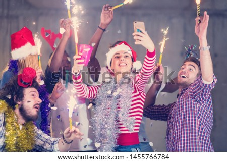 multiethnic group of young happy casual business people taking selfie picture while dancing with sparklers and having fun during new year party in front of concrete wall at new startup office