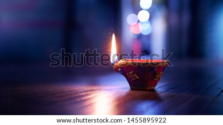 Happy Diwali - Lit diya lamp on street at night #1455895922