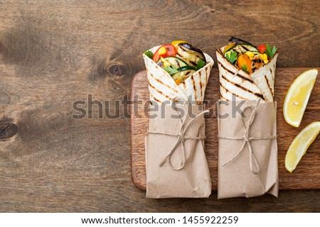 Vegan tortilla wrap, roll with grilled vegetables. Royalty-Free Stock Photo #1455922259