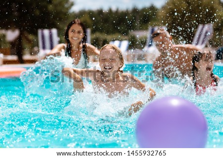 Ball in pool. Cheerful happy parents and children laughing while playing ball in swimming pool #1455932765