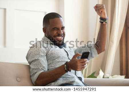 Excited overjoyed black man winner holding smartphone feeling euphoric with mobile online bet bid game win, happy ecstatic african guy looking at cell phone celebrate receiving reading good news #1455947291