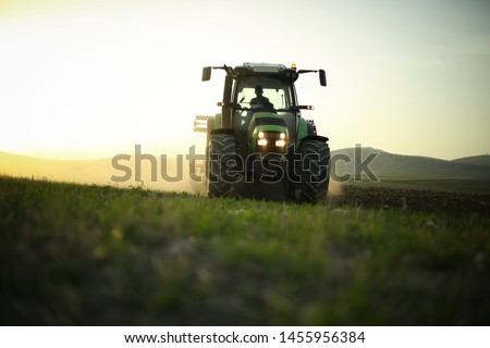in the field, tractor harvesting. Farmer trying to finish sunset works with his tractor. #1455956384