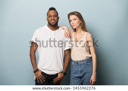 Confident African American man in glasses and woman in casual style clothes, jeans posing together, young fashion diverse models, couple looking at camera, isolated on studio background #1455962276
