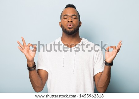 Thoughtful African American man in glasses calming, breathing deep, meditating with closed eyes, mudra gesture, young male practicing yoga, doing exercise, standing isolated on studio background