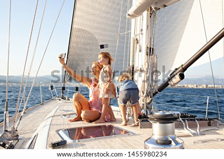 Mother and children on luxury sailing yacht summer holiday sunset trip, taking selfies with smartphone, fun activities outdoors. Family technology on vacation together, leisure recreation lifestyle.