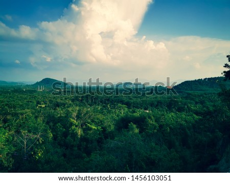 Adjust the color tone in yellow tones. : A large cloud occurred at that time. Which contrasts with the blue sky of the atmosphere. Below are forests and mountains. #1456103051