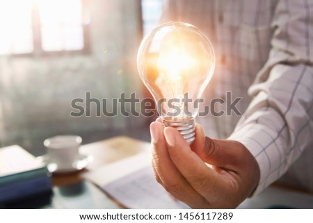 businessman hand holding light bulb in office. concept save energy power #1456117289