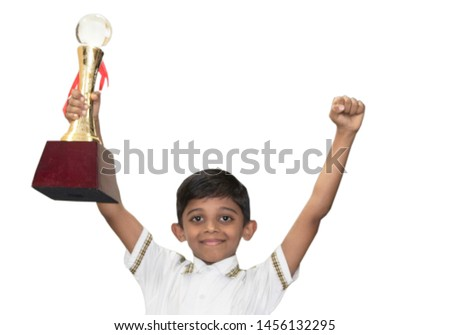 Clever schoolboy raising his trophy as a winner in school competition #1456132295