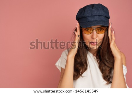 Young brunette puts her yellow sunglasses on looking playfully at the camera #1456145549