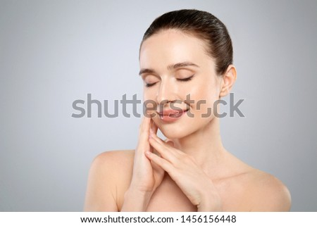 Portrait of beautiful young woman with perfect skin on grey background. Spa treatment #1456156448