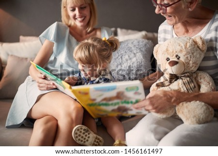 Cute little girl with mom and grandma looking picture book