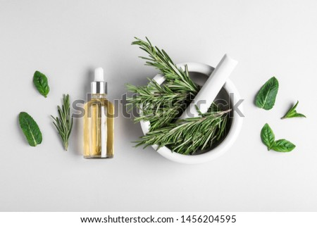 Flat lay composition with herbal essential oil on light background #1456204595