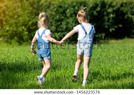 Girls running around the lawn with grass playing with splashes of water to water the plants #1456223576