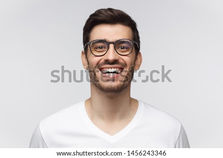 Laughing out loud. Joyful young man in casual t-shirt smiles broadly, laughing, showing perfect white teeth