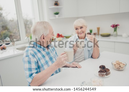 Portrait of sweet cute old lady man sit table telling speaking saying talking hold hand beverage pastry indoors #1456244549