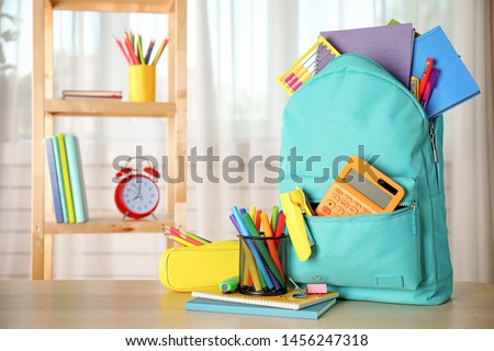 Bright backpack and school stationery on table indoors, space for text Royalty-Free Stock Photo #1456247318