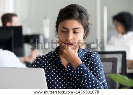Pensive millennial indian employee work at laptop in coworking space think over problem solution, thoughtful young female worker use computer, consider startup project, making decision #1456301078
