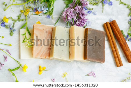 Natural handmade soap bars with organic medicinal plants, cinnamon spice and flowers.Homemade beauty products with natural essential oils from plants and flowers, top view closeup photo #1456311320