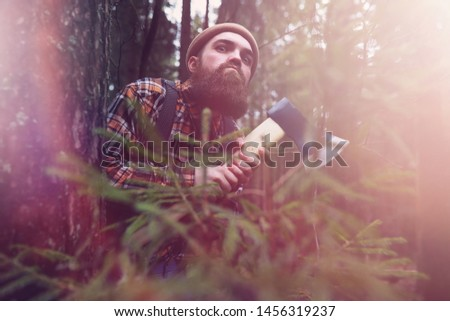 A bearded lumberjack with a large ax examines the tree before felling #1456319237