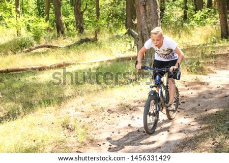 Voronezh, Russia, June 2019: Pine forest, teen boy rides a bicycle along a path in the forest.  The cyclist rides fast through the springboards. #1456331429