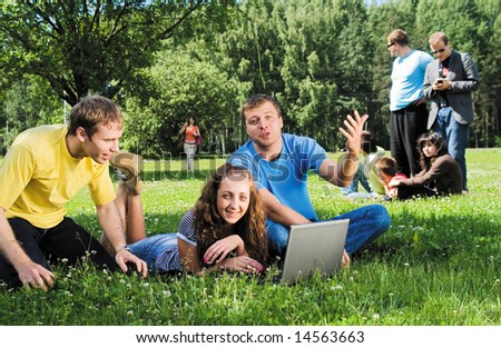 Group of young men and women with laptops enjoy a sun on the meadow #14563663
