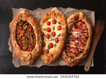 Traditional Turkish baked pide dish. Middle Eastern snacks. Turkish pizza. Three Pides of cheese, meat and bacon. Open pies with different maingame. The view from the top. Copy space. #1456369766