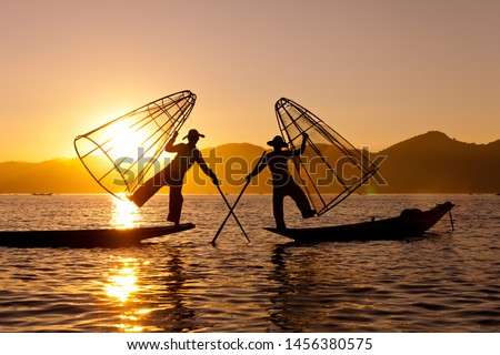 Silhouette of Myanmar fisherman on wooden boat at sunset .Burmese fisherman on bamboo boat catching fish in traditional way with handmade net balancing and paddling with a leg. Inle lake,Myanmar #1456380575