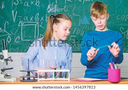 Girl and boy smart students conduct school experiment. School education. Chemical analysis. Kids busy study chemistry. School chemistry lesson. School laboratory. Describe chemical reaction notepad. #1456397813