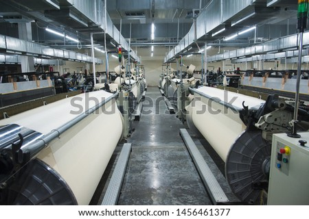 Industrial fabric production line. Weaving looms at a textile factory Royalty-Free Stock Photo #1456461377