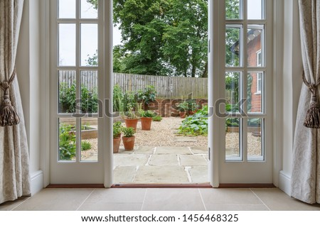 View of garden from inside house with french doors leading to a courtyard kitchen garden #1456468325