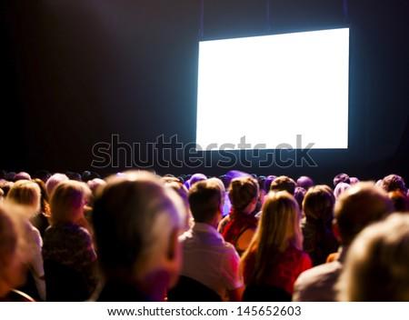 Crowd audience in dark looking at bright screen #145652603